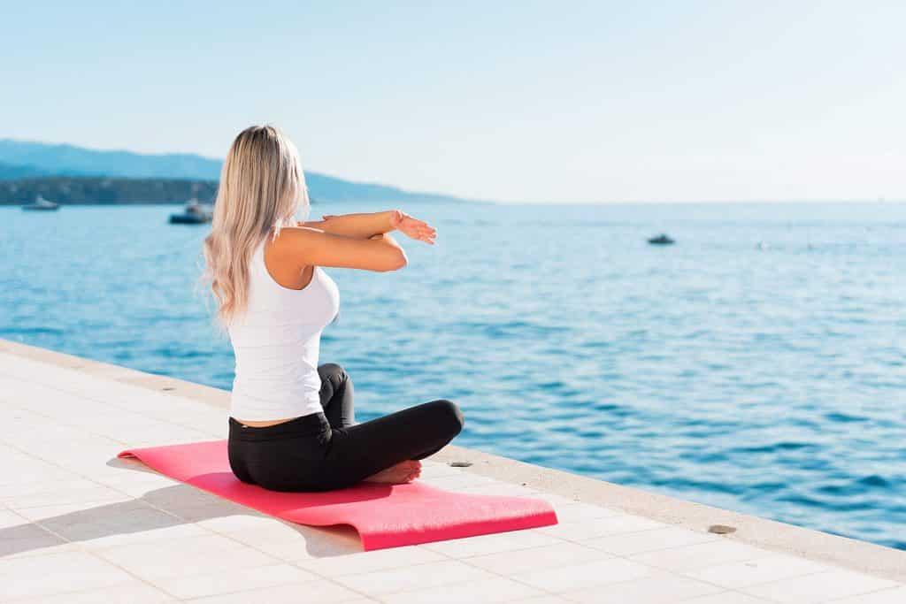 Yogafx International Yoga Teaching Academy Bali woman stretching before morning yoga class
